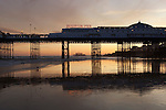 Great Britain, England, East Sussex, Brighton: Sunset behind Brighton Pier with ruins of the West Pier in distance