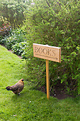 "Orford, Suffolk; sign saying ""books"" and chicken at the charity book shop in Orford."