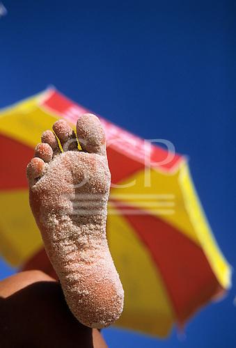 Rio de Janeiro, Brazil. A sandy foot against a parasol on the beach on a sunny day.