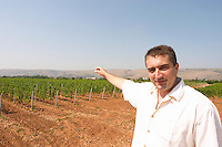 The vineyard with vines on the plain near Mostar with the mountain range in the background. The director manager owner Veselko Cule. Looking out over his vast vineyards. Vranac grape variety. Typical red reddish clay sand sandy soil mixed with pebbles rocks stones in varying amount. Vineyard on the plain near Mostar city. Hercegovina Vino, Mostar. Federation Bosne i Hercegovine. Bosnia Herzegovina, Europe.