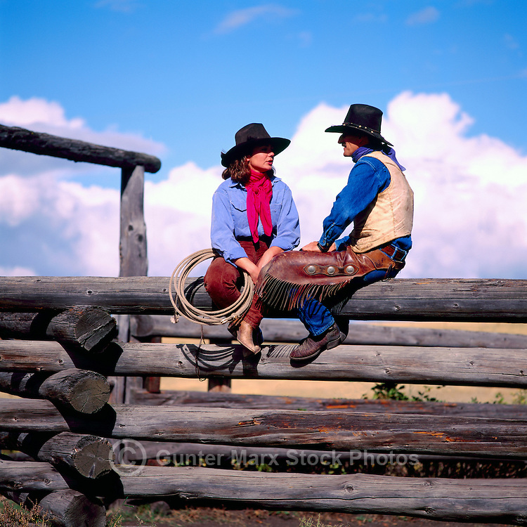 Cowgirl and Cowboy sitting on a Log Rail Fence, British Columbia, Canada