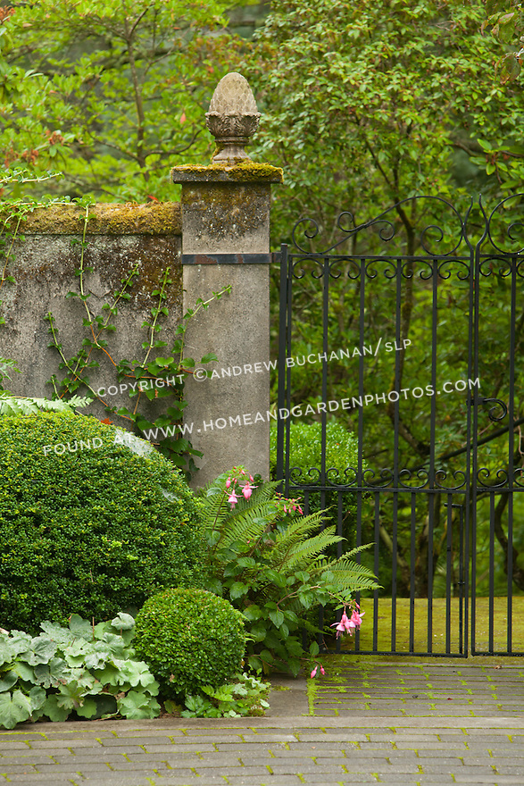 A moss-covered stone pillar and wall join a metal gate at the entrance to a brick courtyard.
