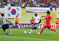 Sylvain Wiltord (11) of France prepares to shoot on Korea Republic goalkeeper Woon Jae Lee (1) as Nam Il Kim (5) defends. The Korea Republic and France played to a 1-1 tie in their FIFA World Cup Group G match at the Zentralstadion, Leipzig, Germany, June 18, 2006.