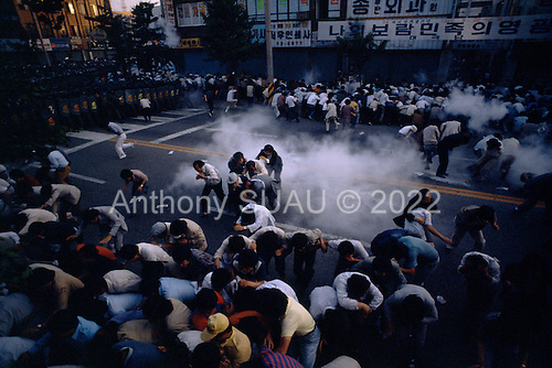 """Chunju, South Korea.May 1986..A peaceful opposition rally is dispersed by riot police with CS tear gas...After two decades of building an economic miracle, in the summer of 1987 tens of thousands of frustrated South Korean students took to the streets demanding democratic reform. """"People Power"""" Korean-style saw Koreans from all social spectrums join in the protests...With the Olympics to be held in South Korea in 1988, President Chun Doo Hwan decided on no political reforms and to choose the ruling party chairman, Roh Tae Woo, as his heir. The protests multiplied and after 3 weeks Chun conceded releasing oppositionist Kim Dae Jung from his 55th house arrest and shaking hands with opposition leader Kim Young Sam. Days later he endorsed presidential elections and an amnesty for nearly 3,000 political prisoners. It marked the first genuine initiative of democratic reform in South Korea and the people had their victory."""