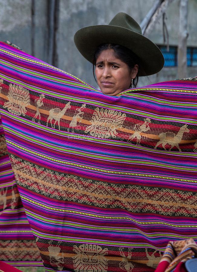 Peru, Urubamba Valley.  Quechua Woman Selling Fabric.