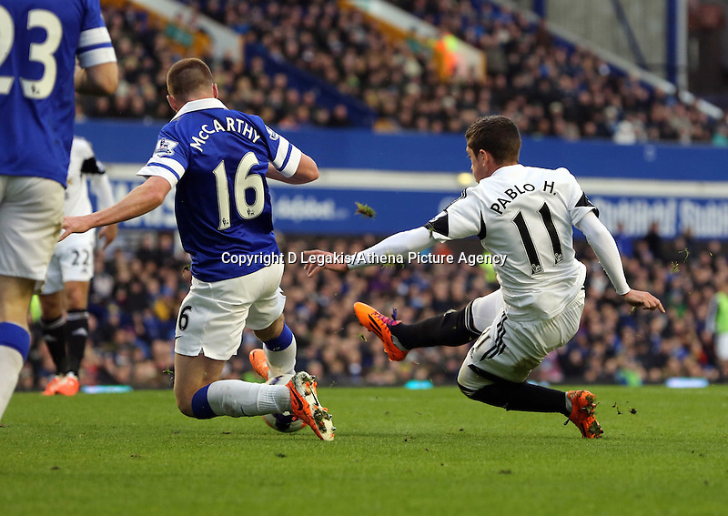 Pictured: Pablo Hernandez of Swansea (R) has his shot blocked by James McCarthy (L) of Everton. Saturday 22 March 2014<br /> Re: Barclay's Premier League, Everton v Swansea City FC at Goodison Park, Liverpool, UK.