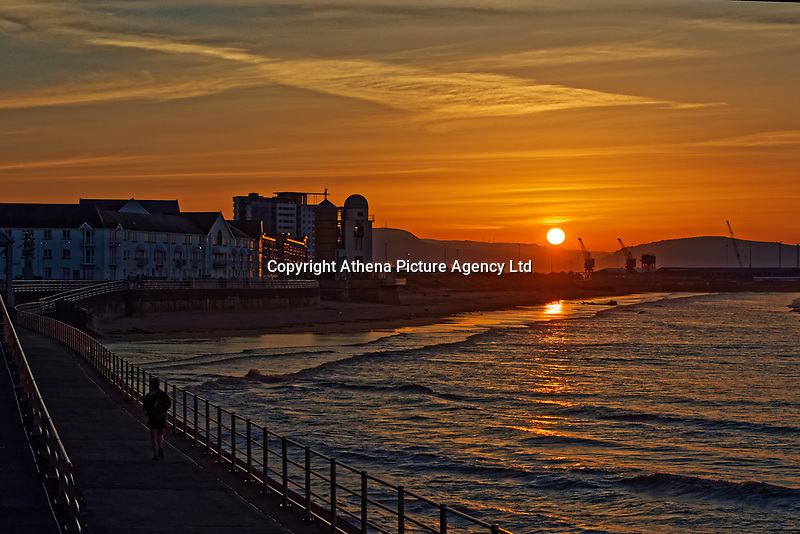 The sun rises over sand dunes and cranes in Swansea Bay, marking the start of another warm and sunny day in south Wales, UK. Wednesday 25 March 2020