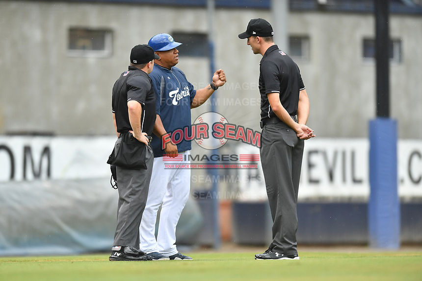 Asheville Tourists manager Robinson Cancel (37) discusses a play with home plate umpire John Budka and first base umpire John Benken during a game against the Augusta GreenJackets at McCormick Field on August 19, 2018 in Asheville, North Carolina. The Tourists defeated the GreenJackets 6-3. (Tony Farlow/Four Seam Images)