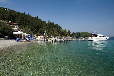 Greece, Corfu, Agni: View of rocky cove, with Taverna, Hotel and boats