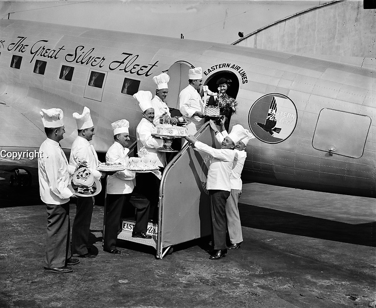 """. Air travelers leaving Washington Airport are being given a special treatmrnt October 1938 during National Air Travel Week, <br /> <br /> Photo by Harris & Ewing.<br /> <br />  <br /> <br /> More info: """"Cakes baked from their favorite recipes are being put aboard each plane by chefs of the leading hotels in the Capitol. Marjorie McKinnon, Eastern Airline hostess, is pictured receiving the delicacies from (left to right) Theophile Homberger, Hotel Hamilton; Eddie Weber, Shoreham; Joseph Cattaneo, Washington; Fritz Meissner, Hay-Adams; Abraham Grob, Wardman Park; Joseph Tucci, Raleigh; Jacques Haerringer, Shoreham; Otto Merz, Willard."""""""