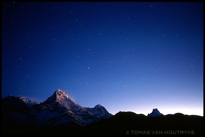 Stars are seen over the Himalayan peaks of Annapurna South (7219m), right, and Annapurna One (8019m), left, before dawn on 1 February 2004.