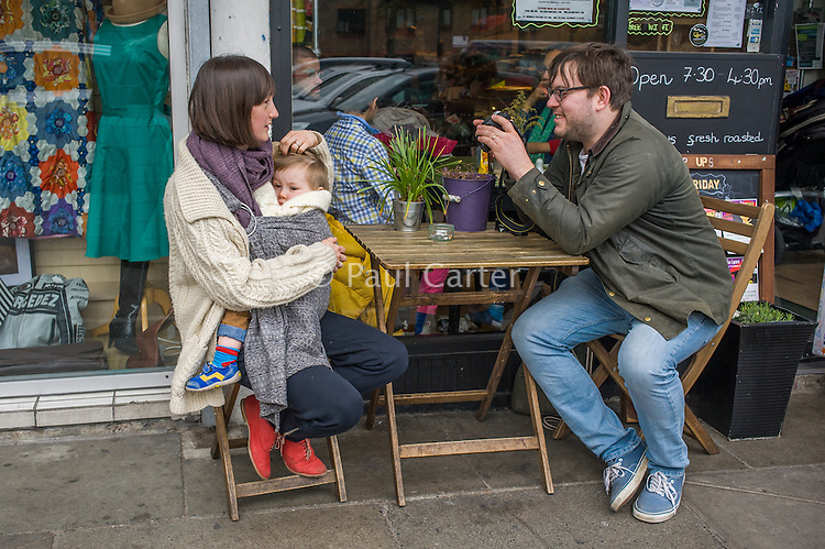 A mother breastfeeds her 15 month old boy from a sling while sitting outside a cafe.  Her partner is looking at a  photograph on the back of his camera that he has just taken of them.<br /> <br /> London, England, UK<br /> 22-03-2015<br /> <br /> © Paul Carter / wdiip.co.uk