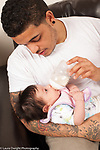 newborn baby girl one month old held by father, drinking from bottle