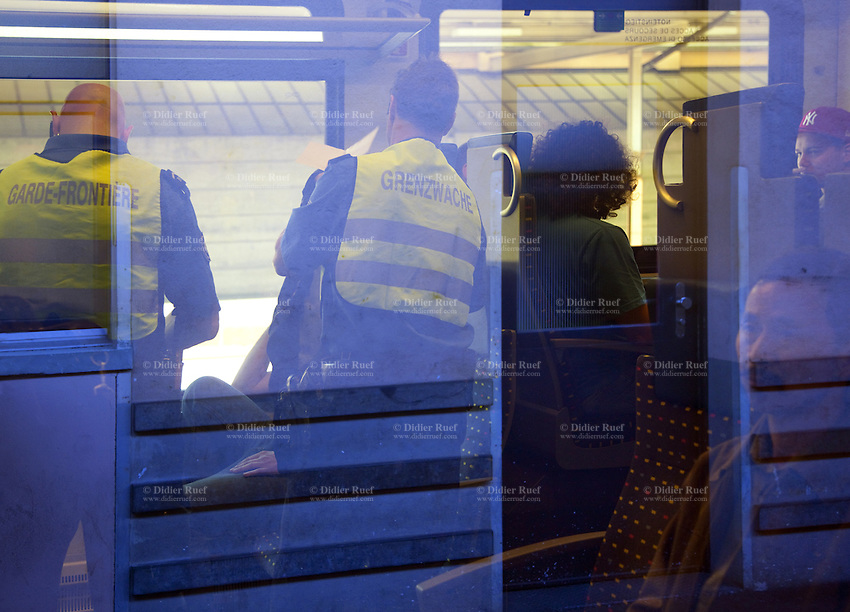 Switzerland. Canton Ticino. Chiasso. Railway station. Two border guards are checking the identity cards from passengers on an intercity train arriving from Italy. About 90 per cent of illegal immigrants who want to get into Switzerland try their chance by train. No specific measures are yet planned by the border guards, but an emergency, reinforcements from other parts of Switzerland is dispatched in Ticino as prevention to a potential massive arrival of economic migrants. 08.04.11 © 2011 Didier Ruef