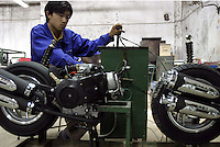 A worker tunes an engine used on LPG scooters at the Shanghai Forever Bicycle Factory in Shanghai, China. With the worsening of the city's air pollution due to increased vehicle traffic, the city has banned the sales of gasoline powered scooters in favor of ones that run on cleaner LPG..21-APR-04