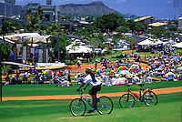 A bicyclist riding by an audience at the Hawaiian slack key guitar festival
