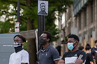 Three men stand beneath an illustration of George Floyd during a march against police brutality and racism in Washington, D.C. on Saturday, June 6, 2020.<br /> Credit: Amanda Andrade-Rhoades / CNP/AdMedia