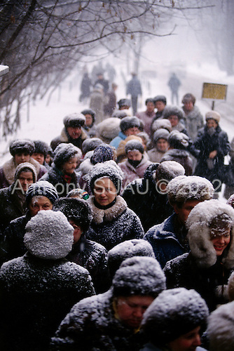 """Moscow, Russia<br /> Soviet Union<br /> December 9, 1991<br /> <br /> People line up to buy sugar during a snow storm. A typical scene from the days in the former Soviet Union. <br /> <br /> In December 1991, food shortages in central Russia had prompted food rationing in the Moscow area for the first time since World War II. Amid steady collapse, Soviet President Gorbachev and his government continued to oppose rapid market reforms like Yavlinsky's """"500 Days"""" program. To break Gorbachev's opposition, Yeltsin decided to disband the USSR in accordance with the Treaty of the Union of 1922 and thereby remove Gorbachev and the Soviet government from power. The step was also enthusiastically supported by the governments of Ukraine and Belarus, which were parties of the Treaty of 1922 along with Russia.<br /> <br /> On December 21, 1991, representatives of all member republics except Georgia signed the Alma-Ata Protocol, in which they confirmed the dissolution of the Union. That same day, all former-Soviet republics agreed to join the CIS, with the exception of the three Baltic States."""