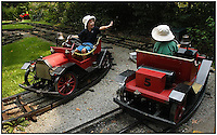 Two children wave to one another while driving cars on an amusement park ride. Model released image can be used for multiple purposes.