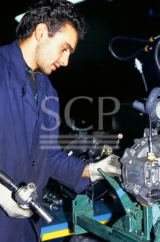 Varna, Bulgaria. Worker in blue overalls assembling a clutch and gearbox.