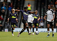 23rd May 2021; Craven Cottage, London, England; English Premier League Football, Fulham versus Newcastle United; Allan Saint-Maximin of Newcastle United passing the ball into midfield while being marked by Joshua Onomah of Fulham