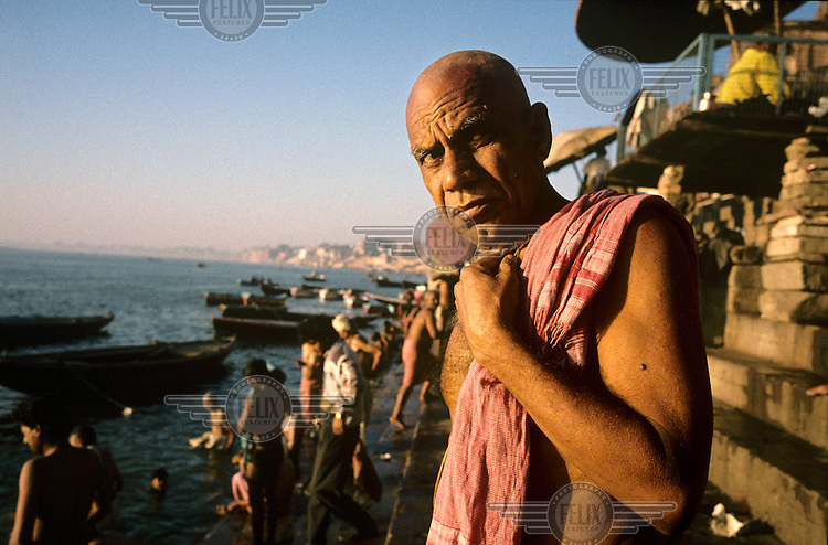 A man on a bathing ghat by the sacred River Ganges (Ganga).