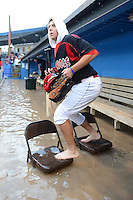 Batavia Muckdogs outfielder Austin Dean (3) uses a bridge made of chairs after the dugout flooded during a brief but heavy rain storm during a game against the Hudson Valley Renegades on August 8, 2013 at Dwyer Stadium in Batavia, New York.   The game was called due to unplayable field conditions.  (Mike Janes/Four Seam Images)