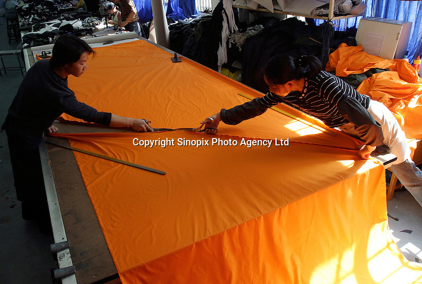 Two workers cut large fabric pieces at the Shengyuan Clothing Factory in Suzhou, Jiangsu Province, China. The factory employs a total of 250 workers that works year-round to fill clothing orders from Adidas and has expanded its operations to a more rural area of the province to meet the demand and cut down labor cost..16-OCT-04