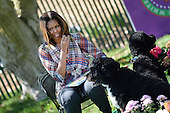 United States first lady Michelle Obama reads the story My Garden to children during the annual White House Easter Egg Roll on the South Lawn of the White House April 21, 2014 in Washington, DC. President Barack Obama and first lady Michelle Obama hosted thousands of people during the annual celebration of Easter. With her are Bo and Sunny, the Obama family dogs.<br /> Credit: Olivier Douliery / Pool via CNP
