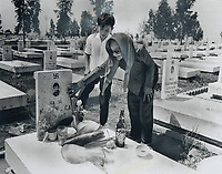 1973 FILE PHOTO -<br /> <br /> Relatives place offerings of food and drink on a grave in the national military cemetery at Bien Hoa; South Viet Nam; where headstones are marked with swastika; a Buddhist religious emblem and an ancient symbol of infinity. Despite the ceasefire; sporadic fighting is continuing throughout South Viet Nam.
