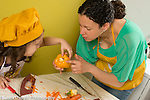 5 year old girl in kitchen with mother learning how to cut vegetable sweet pepper