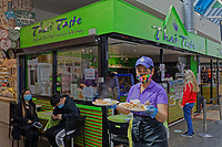 Pictured: A member of staff ready to serve customers with food at the Thai Taste restaurant in Swansea Indoor Market, Wales, UK. Monday 17 May 2021<br /> Re: Restrictions implemented by the Covid-19 Coronavirus pandemic, have been relaxed with hospitality business being allowed to open their indoors spaces in Wales, UK.