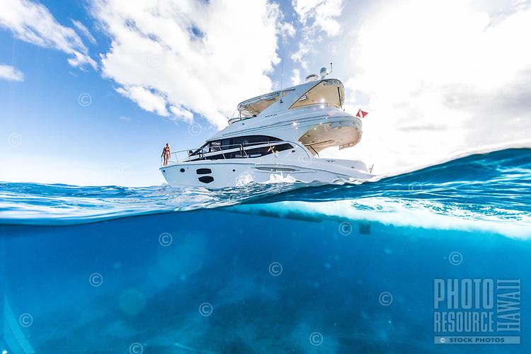 Friends enjoy a sunny day aboard a white power cruiser near Waikiki, O'ahu.