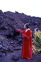 Elderly woman in red dress throwing gin for the goddess Pele into lava bed. Hawaii volcanoes national park, Big island