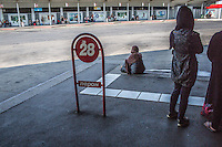migranti in attesa a una fermata del bus <br />
