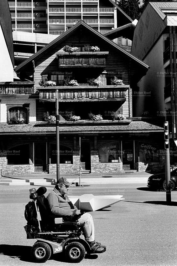 Switzerland. Valais. Crans Montana. A man seated on his motorized wheelchair passes in front of a traditional wooden chalets and new modern buildings. A motorized wheelchair, powerchair, electric wheelchair or electric-powered wheelchair (EPW) is a wheelchair that is propelled by means of an electric motor rather than manual power. Motorized wheelchairs are useful for those unable to propel a manual wheelchair or who may need to use a wheelchair for distances or over terrain which would be fatiguing in a manual wheelchair. They may also be used not just by people with 'traditional' mobility impairments, but also by people with cardiovascular and fatigue-based conditions. 13.08.2017.  © 2017 Didier Ruef