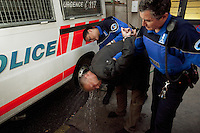 "Switzerland. Geneva. A police officer and a policewoman rinse the face of a caucasian man with water at the Paquis police station. The man was arrested because he has refused to pay a prostitute, who sprayed his face as retaliation. The man is completely drunk. A police station or station house is a building which serves police officers and contains offices, temporary holding cells and interview/interrogation rooms.  Pepper spray, also known as OC spray (from ""Oleoresin Capsicum""), OC gas, and capsicum spray, is a lachrymatory agent (a chemical compound that irritates the eyes to cause tears, pain, and even temporary blindness) used in policing. Its inflammatory effects cause the eyes to close, taking away vision. 31.03.12 © 2012 Didier Ruef.."