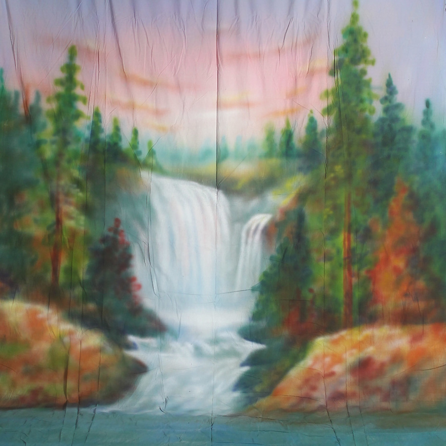 Backdrop featuring natural waterfall scene in wilderness with trees and rocks at sunset