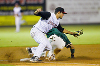Kannapolis Intimidators third baseman Nick Basto (27) fields the throw from the catcher as Jesus Solorzano (12) of the Greensboro Grasshoppers steals third base at CMC-Northeast Stadium on July 12, 2013 in Kannapolis, North Carolina.  The Grasshoppers defeated the Intimidators 2-1.   (Brian Westerholt/Four Seam Images)