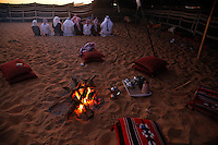 The Al Mansori family prays at sunset near the campfire at the contest compound.  This family is from about 50KM outside Abu Dhabi.  They walked their camels even though they are wealthy, they did not want to risk transport in trucks for their precious camels.  The patriarch won a car today and another camel got a first place (up to a million DRH).