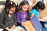 Education Preschool  three girls sitting side by side looking at picture books
