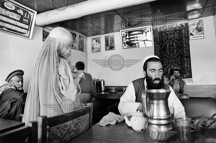 A woman wearing a burkha begging in a tea-house. Many women have been left destitute having been widowed during the war, deprived of an education and then forbidden to work by the Taliban.