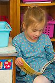 MR / Schenectady, NY. Zoller Elementary School (urban public school). Kindergarten inclusion classroom. Student (girl, 5) reading a book at learning center time. MR: Bog2. ID: AM-gKw. © Ellen B. Senisi.