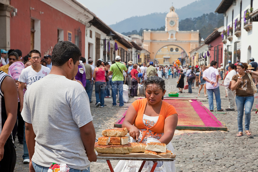 Antigua, Guatemala.  Street vendor selling corbata, a sweet made of wheat flour, during Holy Week, La Semana Santa.  Behind her is an alfombra (carpet) under construction.  In the background is the Santa Catalina Arch, a historic landmark of Antigua.