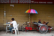 A local eat his lunch while a rickshaw driver takes rest outside a kopitiam in capital Georgetown of Penang in Malaysia, India. Photo: Sanjit Das/Panos