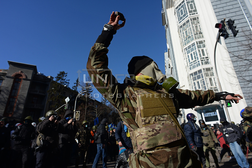 A protester wearing war gear anf a gas mask throws paving stones towards the police. Kiev, Ukraine
