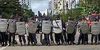 Police in riot gear block a road on the 11th day of protests calling for the overthrow of the country's military junta.