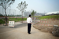 """CHINA. Beijing. A man trying to catch a glimpse of the new Olympic park. In recent years construction has boomed in Beijing as a result of the country's widespread economic growth and the awarding of the 2008 Summer Olympics to the city. For Beijing's residents however, it seems as their city is continually under construction with old neighborhoods regularly being razed and new apartments, office blocks and sports venues appearing in their place. A new Beijing has been promised to the people to act as a showcase to the world for the 'new' China. Beijing's residents have been waiting for this promised change for years and are still waiting, asking the question """"Where's the new Beijing?!"""". 2008."""