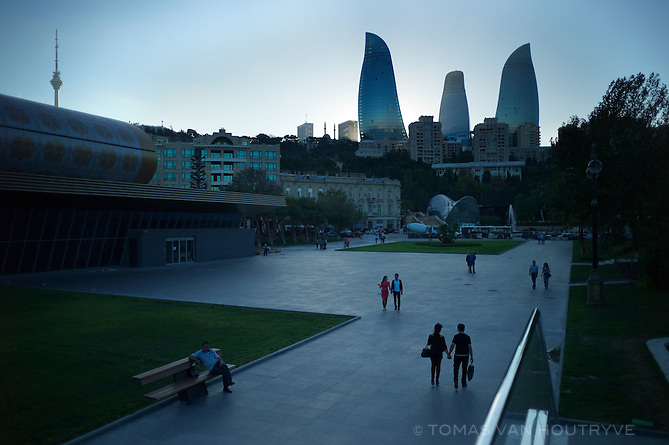 People walk along the seaside park know as Bulvar in front of the newly constructed Flame Towers in Baku, Azerbaijan.