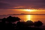 People on rocks at sunset at Rosario Beach, Deception Pass State Park, Fidalgo Island, Washington. .#2414-0413